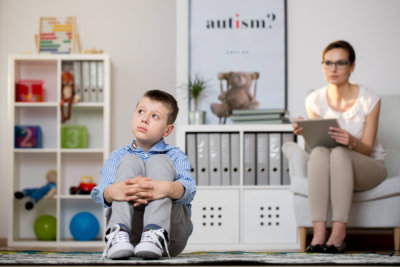 Psychologist in glasses is looking at kid sick of autism