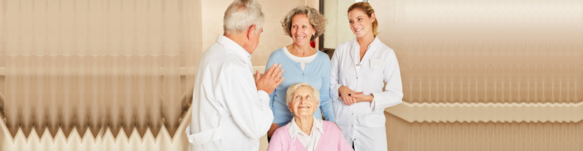 Doctor talking to senior women in rehab and daughter on the hospital corridor