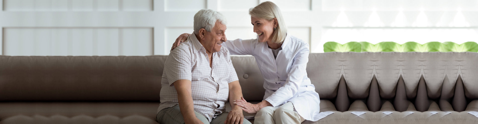Friendly mature general practitioner communicating with senior patient, sitting together on sofa.